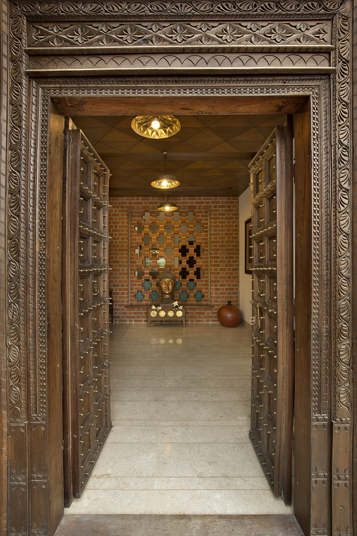 Carved wooden door befitting for a pooja room designed by KN Associates / Photography by Tejas Shah