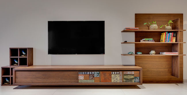 A wooden wall mounted TV unit design with no back paneling.But the unit below has intricate details and there is additional display unit comprising floating shelves on the side.