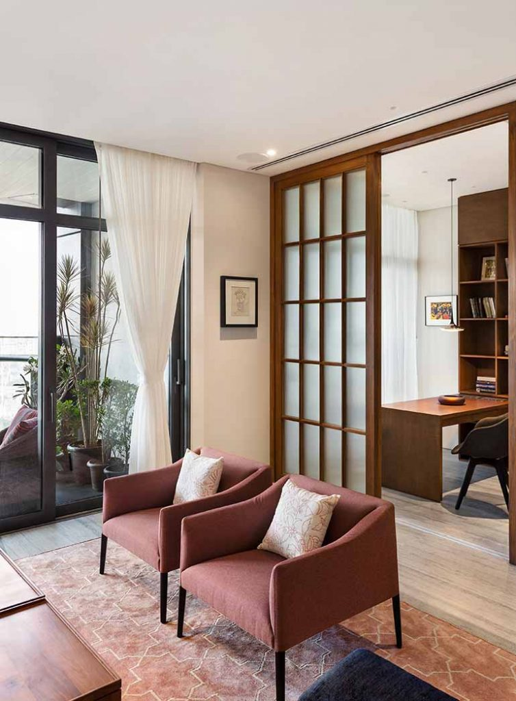 The bedroom sandwiched between the other two rooms has been conceived as a flexible multi-use space. A movable glass door separates the living space from this room.