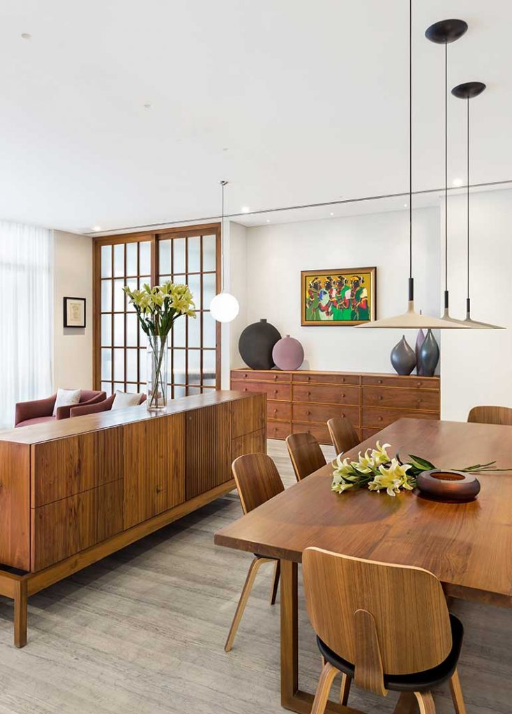 A large wooden storage cabinet serves as the partition between the living and dining area while another chest of drawers sits on the far end in the niche