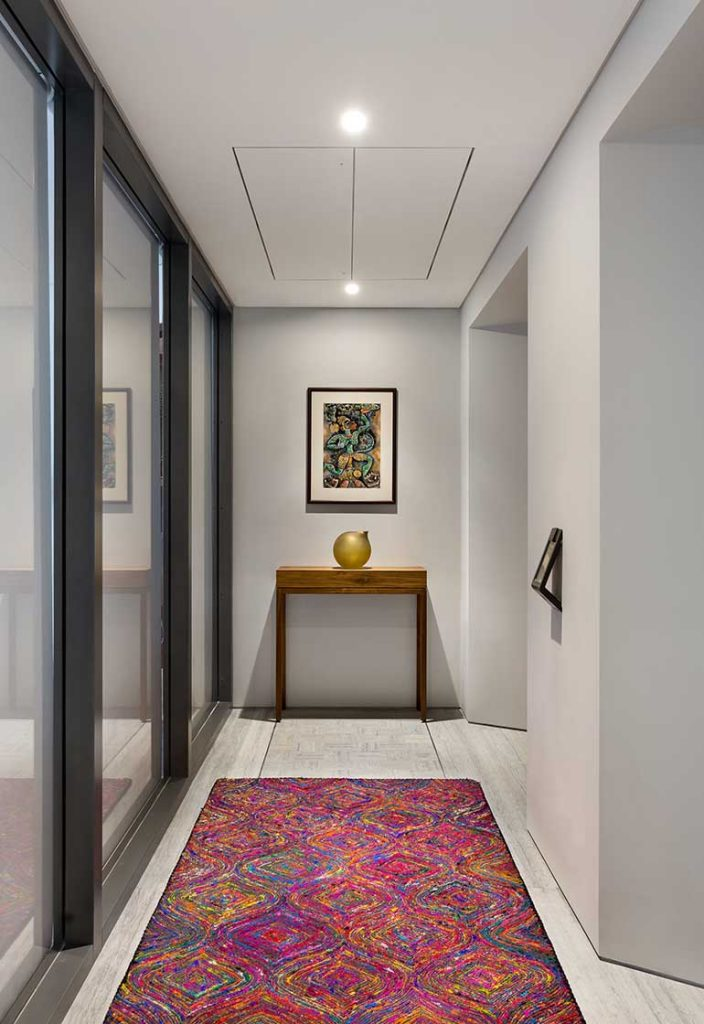 The fluted glass infill used for all the doors of the apartment, allow natural light to seep into its depths.  The wall treatment is light and neutral to allow better reflection of light and illuminate even dark corners like this passageway between the rooms.