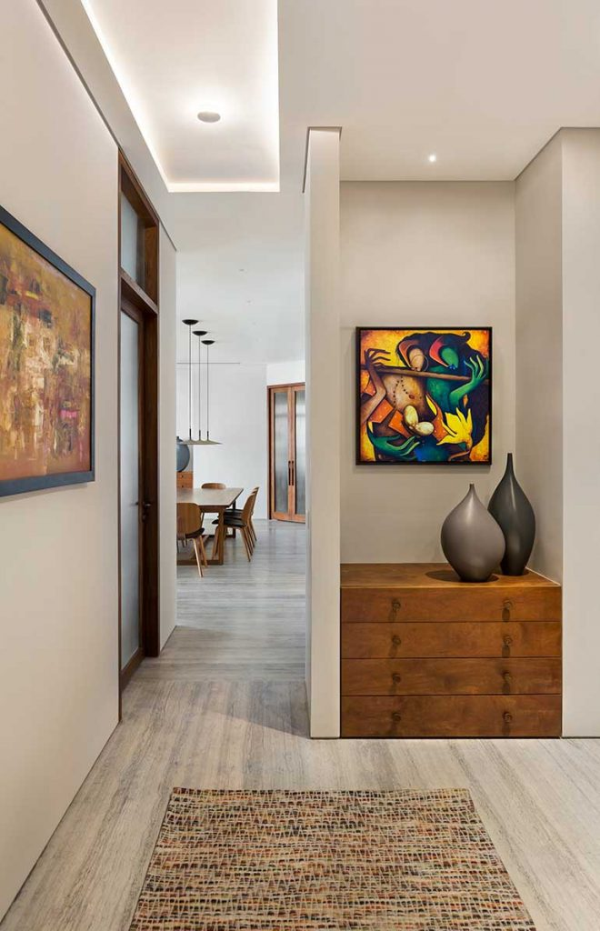 Bold, vibrant artworks on all the niches and the walls draws the eyes away from the otherwise neutral palette and storage.