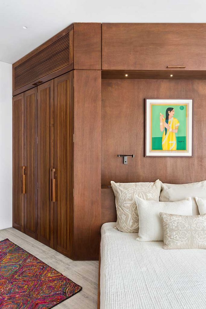 The bedroom showcases floor to ceiling wardrobes in wood. The furnishing and artwork in this room has a  soft, feminine touch