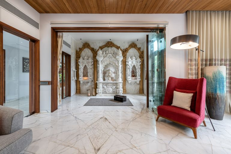 An enclosed pooja room in intricately carved white marble is nestled between the living area and the family room.