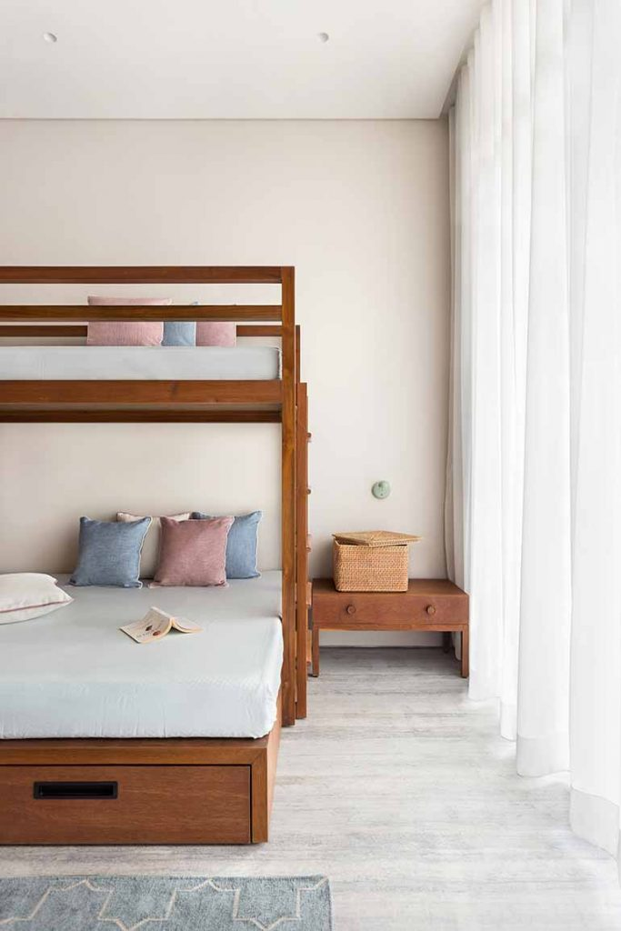 A wave of minimalism in stark contrast to the rest of the house takes over the girl's room . A bunk bed with storage doesn't seem overwhelming thanks to the pastel furnishings.