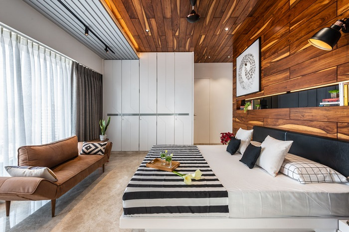 Master bedroom: the rest of the room wears a minimalist look in to sober up the bold veneer panelling going behind the bed and coming along the ceiling too which is an accent wall.