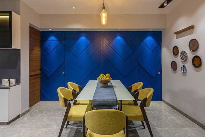 A cobalt blue textured accent wall in the dining is bold in contrast to the muted living space. A cluster of three filament pendant bulbs gives it a subdued touch.  The dining table and  chairs with yellow tapestry are custom-made.