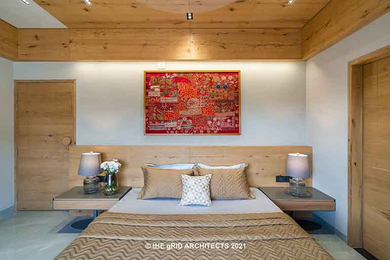 A vibrant artwork hangs above the bed in this minimalist bedroom dressed in natural wood tones.