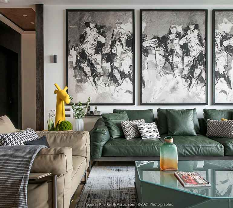 Solid colored green sofa in living room with monochromatic art.