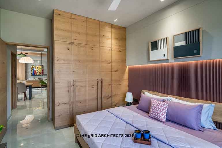 The grains and stains in this understated wardrobe stands tall - both figuratively and literally in this compact bedroom. One gets a sneak peek into the living room from here.