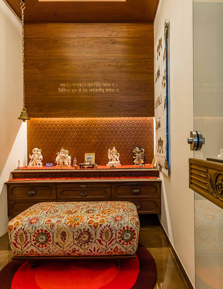A compact pooja room with storage and beautifully engraved gilded shloka against a wooden back panel.