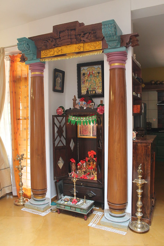 The wooden pillars give this otherwise compact pooja room a grandiose look.
