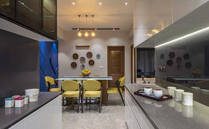 A view of the dining from the open kitchen. The sleek contemporary kitchen cabinets sport metallic, glossy acrylic finish. The countertop is made of quartz. The handle-less cabinets with a glass-like back splash give it a modern edge, much in contrast with the dining in the backdrop.