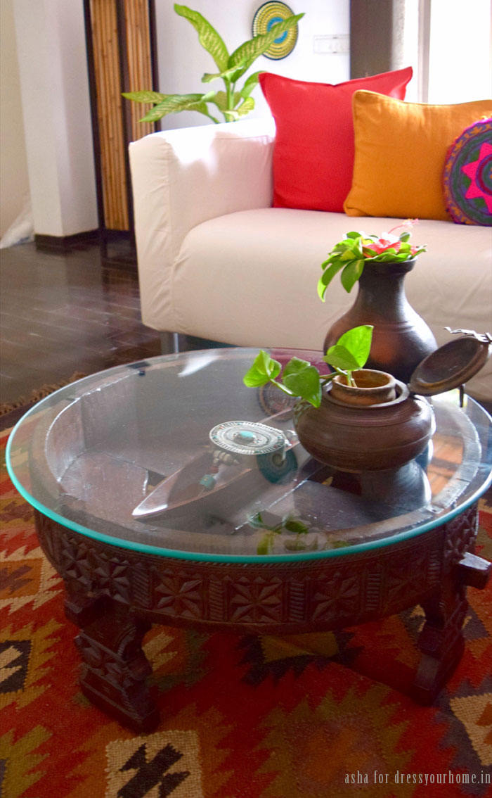 A chakki table doubles as the coffee table. Asha styles it using a necklace with a large pendant. The round wooden planter is an old jewellery box.