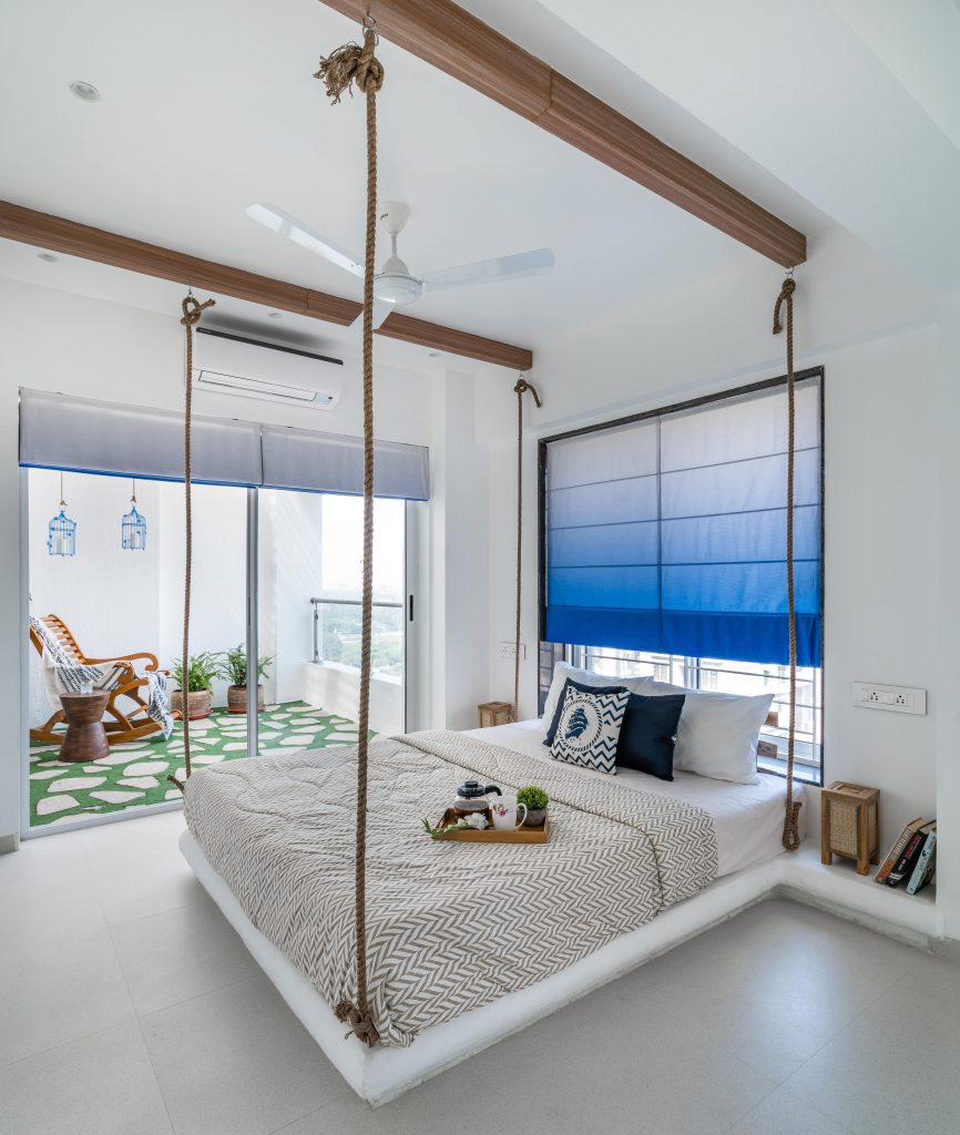 Ropes dangling from the ceiling give the impression of anchoring the bed. It was added to give a rustic vibe.  Designed by Pune based interior design firm Between Walls.