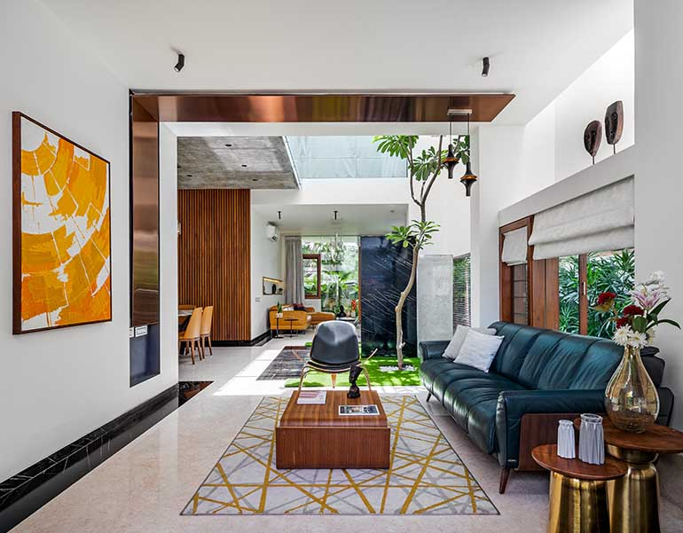 Formal living room with green couch and internal courtyard in Bangalore. Vaastu compliant home.