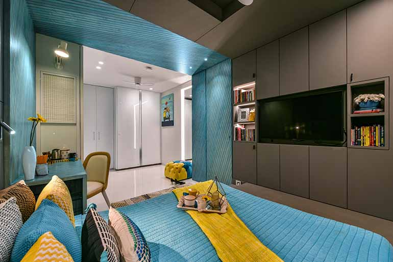This bedroom has enough storage that is camouflaged. Designer's tip: for smaller bedrooms, pushing the bed to the window frees up the space for movement making the space appear larger when it reflects from large mirrors.
