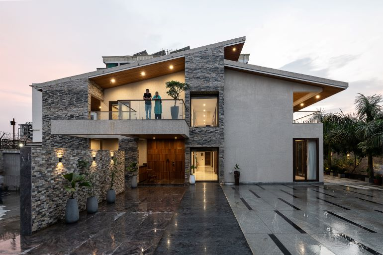 The facade of the home with the family enjoying the view of the greenery from the deck.