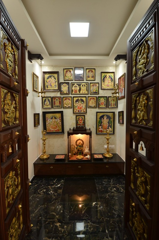 Pooja room with door containing embossed images of gods and goddesses. Tanjore paintings on the wall.