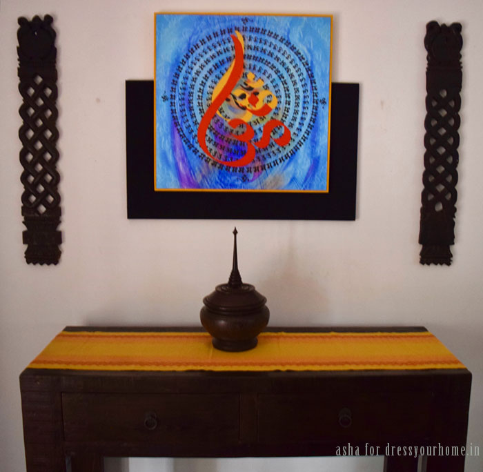 Inside another corner of the living room is a poster framed in an abstract design. It is flanked by old wooden spoon holders from Kerala. The bowl on the console table is from Thailand.