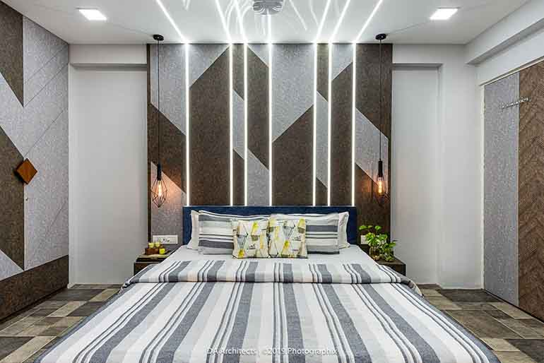 A simple bed back highlighted with profile lights give a unique identity to this grey themed room. The large wardrobes are designed in such a way that gives an effect of a feature wall & breaks the monotony of the typical wardrobe designs.