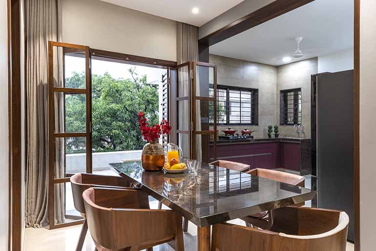 An open plan layout of the kitchen and dining. The dining has a breathtaking view of the greenery outside.