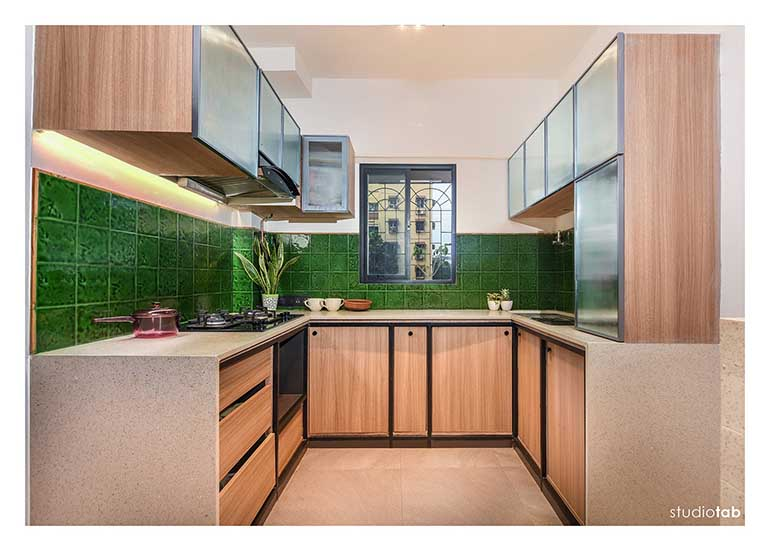 A terrazzo counter top + bottle green ceramic tiles add the required freshness to the kitchen. ever nook is made used of in this kitchen.