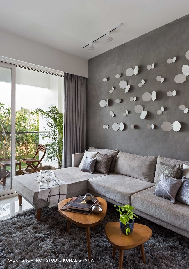 Gray textured washed walls in living room give it a rustic look with artificial butterflies