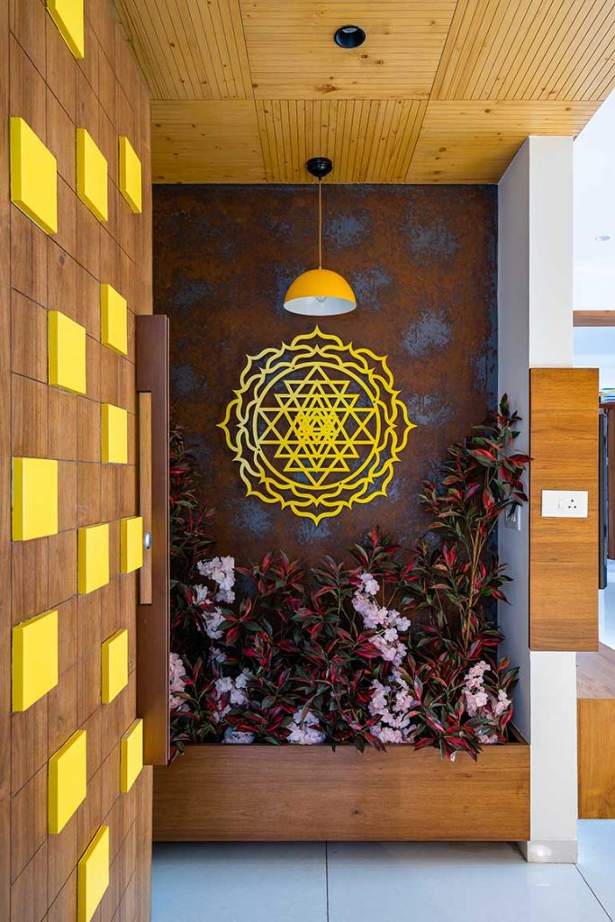 The foyer has an yellow coloured Sri Yantra with a textured wall behind it to give positive energy.