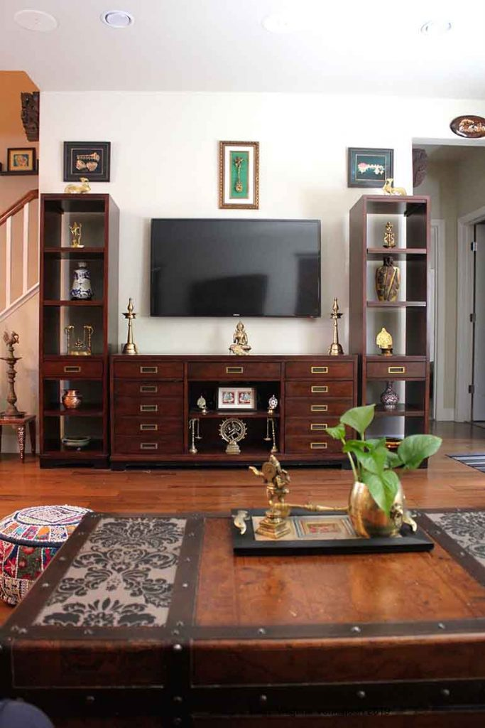 The pieces around the entertainment unit weave a story of their own. dancing Ganesha spoon mounted above the entertainment center is flanked by two gold foiled paintings of musical instrument to symbolize Ganesha dancing in joy and harmony to the music.