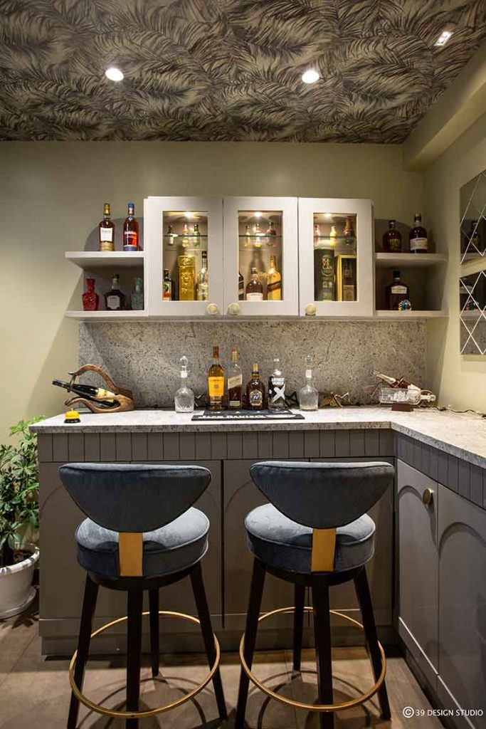 A compact bar area with moody design and painted ceiling.