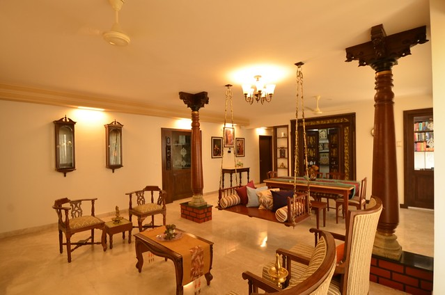 A glimpse of the antique pooja door, wooden pillars, and teak furniture in this living room.