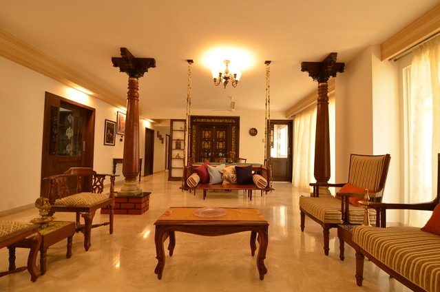 Wooden furniture, pillar and swing complete this Chettinad  house inspired living room.