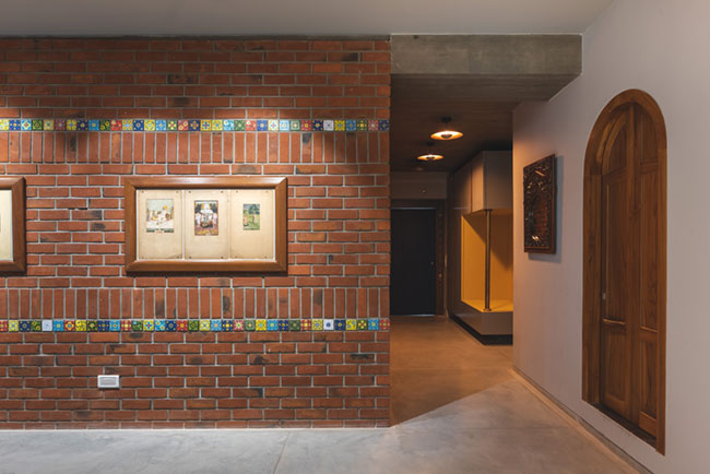 35-foot long exposed brick wall in living room to hold the artwork