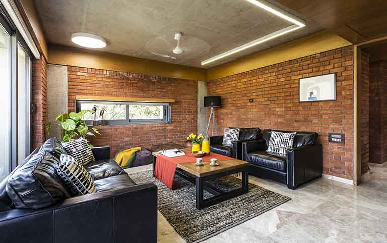 The exposed concrete ceiling complements the rustic look of the brick walls.