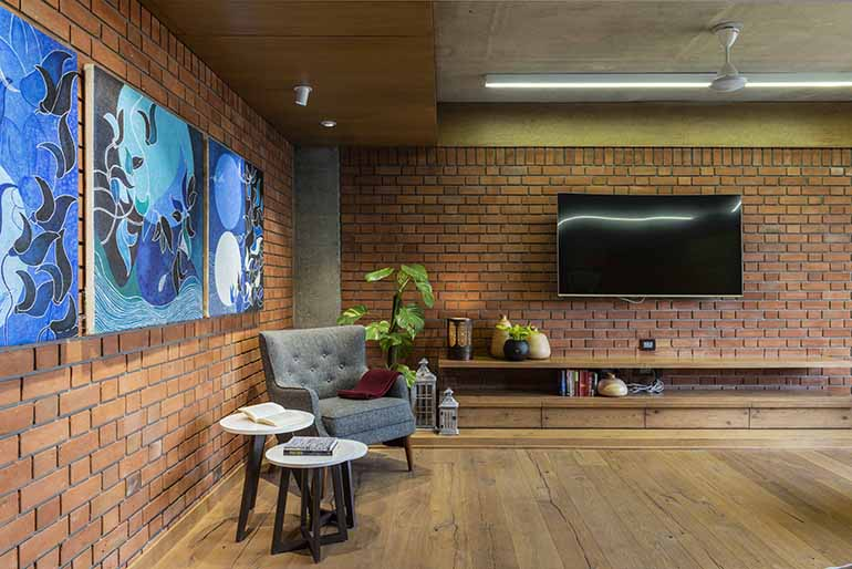 The brick wall serves as a great backdrop to several abstract artworks around the apartment.