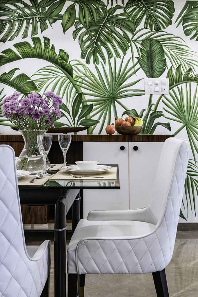 An urban jungle dining room with foliage wallpaper.