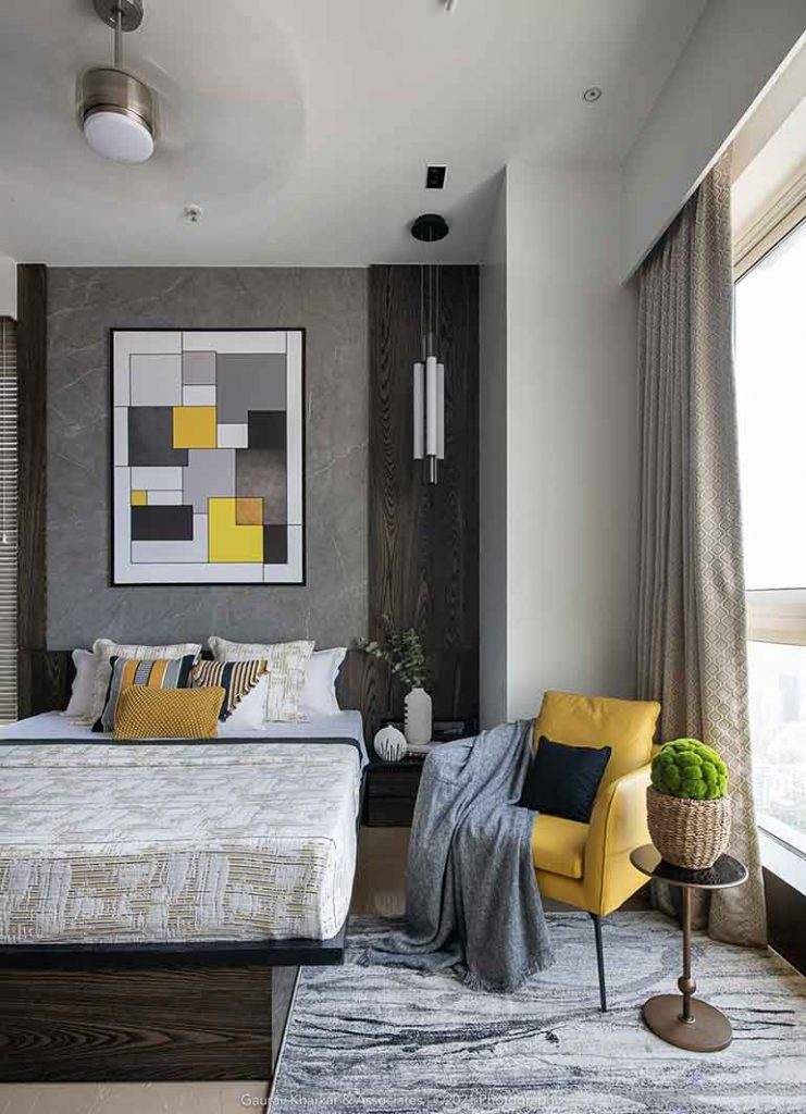 Yellow and grey modern art in the master bedroom of a 3 BHK apartment in Mumbai.