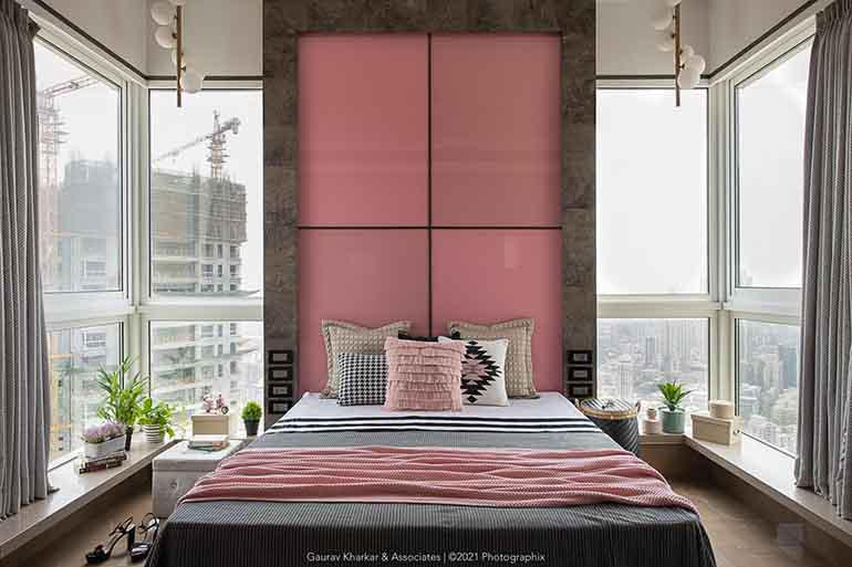 A back painted pink glass serves as a headboard for the daughter's bedroom. The large windows enveloping the room offer breathtaking views of the city.
