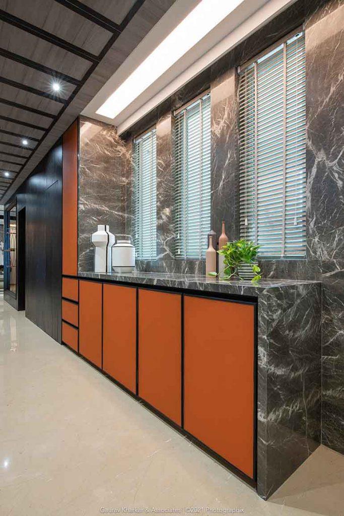 3 BHK apartment interiors in Mumbai: Passage area with storage cabinets dressed in orange.
