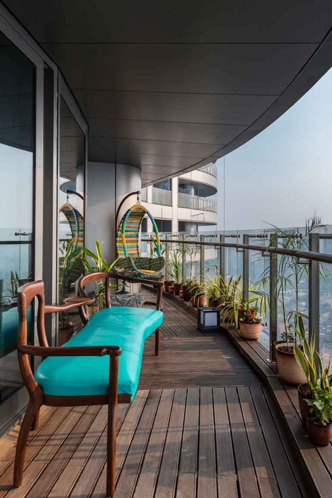 This unique custom-made wooden bench in turquoise and the colourful swing by Retyrement Plan complete the relaxing zone in the balcony.