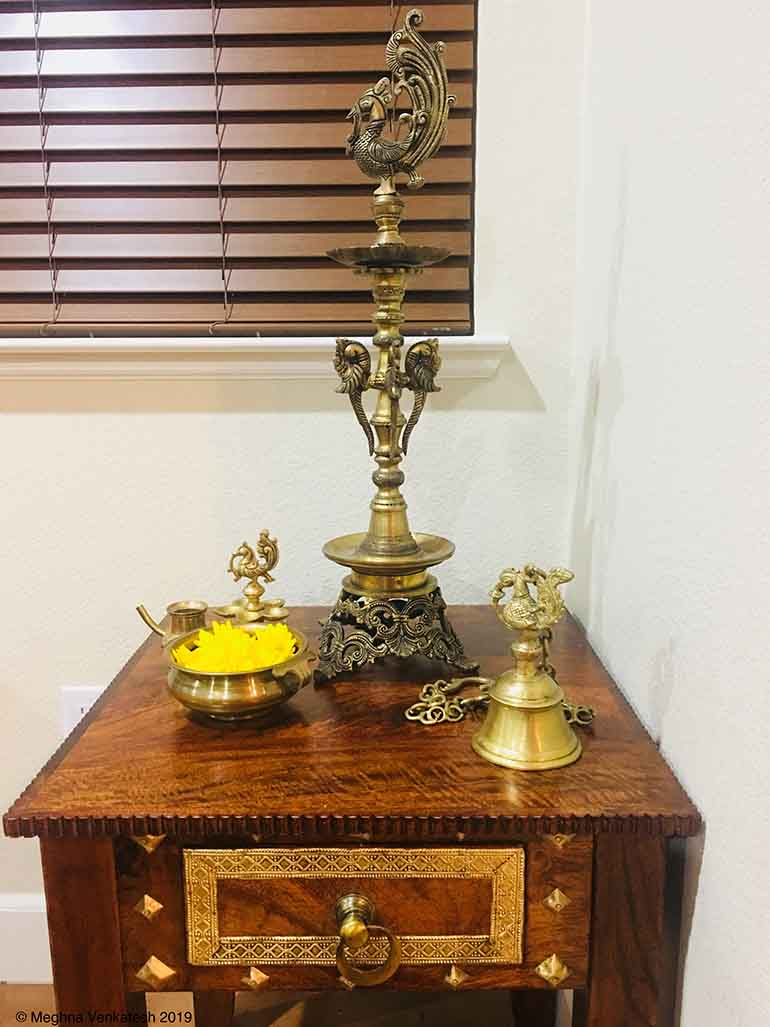 The Pier 1 side table holds a peacock diya and other artifacts like an uruli, a kamandalu, and a peacock bell.