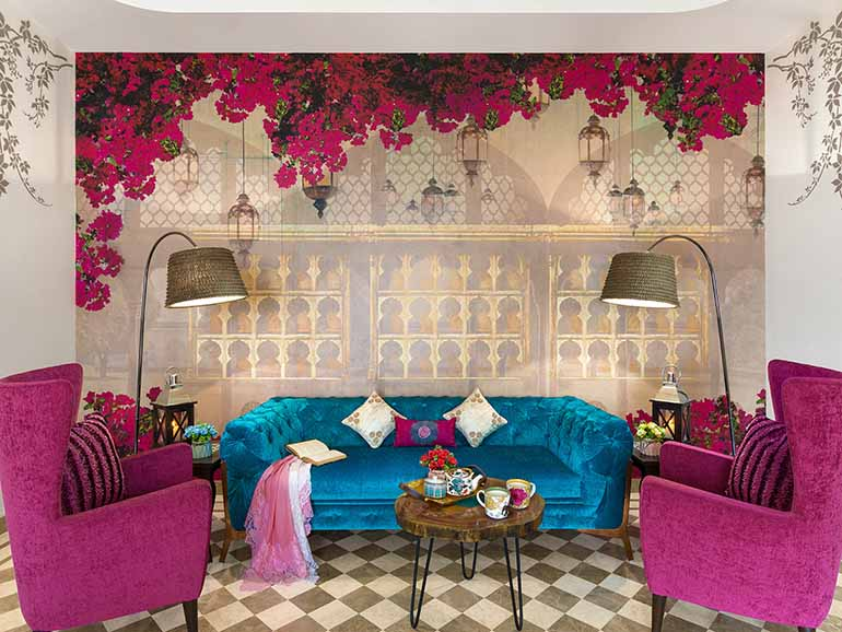 The lounge area with Bougainvilla wallpaper with matching accent chairs, turquoise upholstered sofa - it's about as royal as it gets.