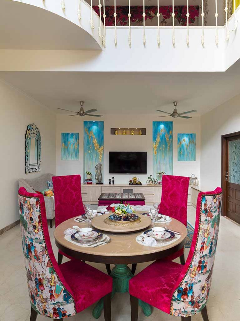 The compact dining adjoining the living reinforces the turquoise + pink theme.