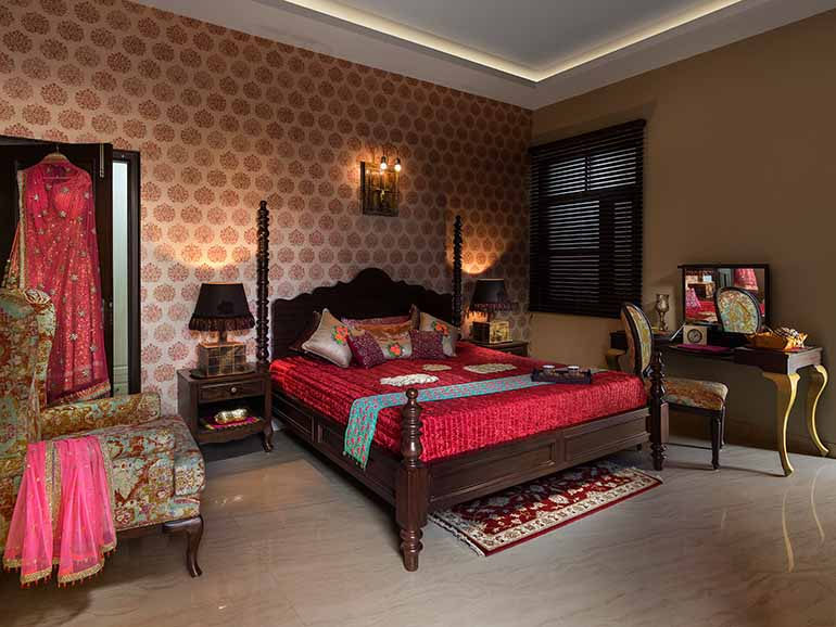 A four post bed made in hard teak wood with a rich wallpaper behind flanked by handcrafted lamps. This room is befitting and a tribute to the style of the royals.