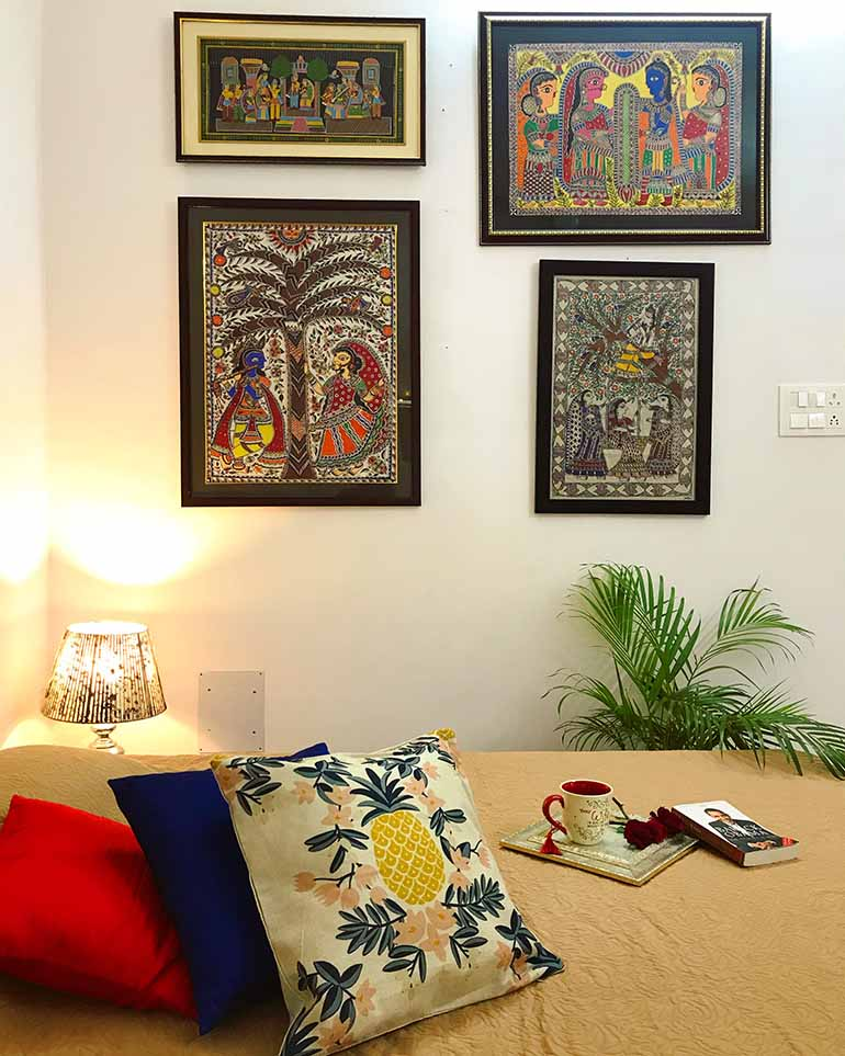 Madhubani paintings sourced locally form a mini gallery wall. Sources: Cushion cover from Decorkart and lamp is from a local shop.