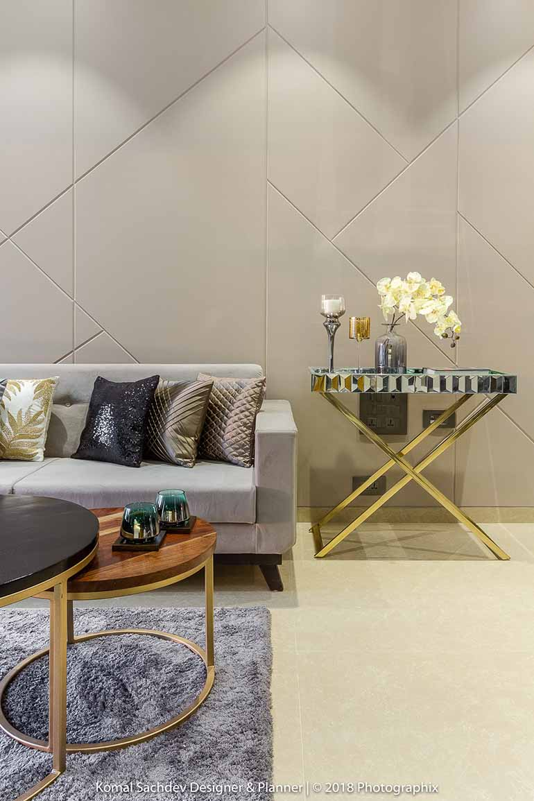 Alternating wooden and metallic center tables with a complementing side table adds a luxurious touch. The grey couch blends with the wall colour.