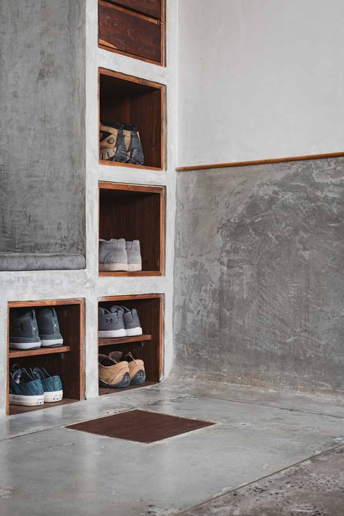 Close up details of the open shoe rack with the concrete bench at the entryway.