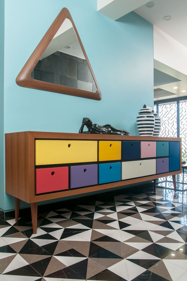 A colourful sideboard frames the entryway of this vibrant Mumbai apartment