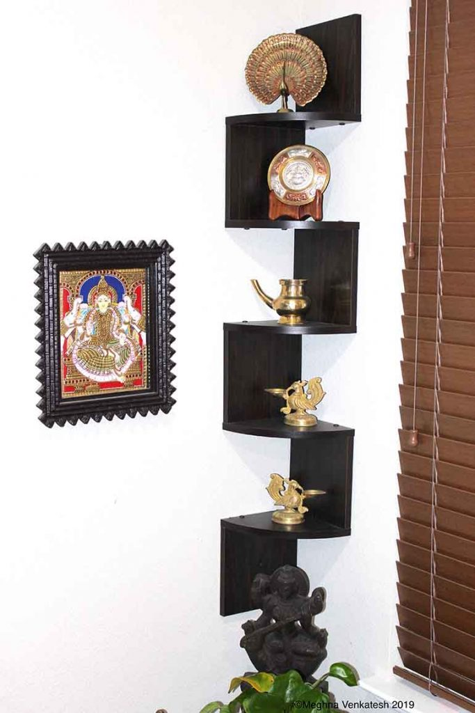 The Pier 1 side table holds a peacock diya and other artifacts like an uruli, a kamandalu, and a peacock bell. There is a side table with a wooden statue of Saraswathi and a kamandalu also filled with pothos and seasonal flowers. A winding corner shelf on the wall holds other traditional brass artifacts. A peacock diya stands on a decorative elephant table by the side of the entertainment center and a dancing Ganesha statue stands on a brass stand by the piano.